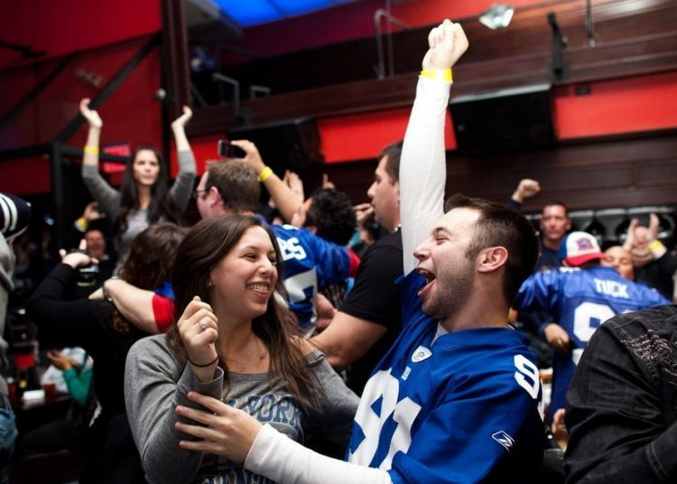 Rachel Margolis, left, and Nathan Tondow, right, celebrate a New York Giants win against the New England Patriots while watching the broadcast of the NFL football Super Bowl in a midtown Manhattan bar, Sunday, Feb. 5, 2012, in New York. (AP Photo/John Minchillo)