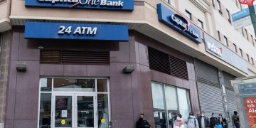 April 20, 2020- Long line of people waiting to withdraw money seen at Capital One Bank in Fordham Heights section of the Bronx (Shutterstock)
